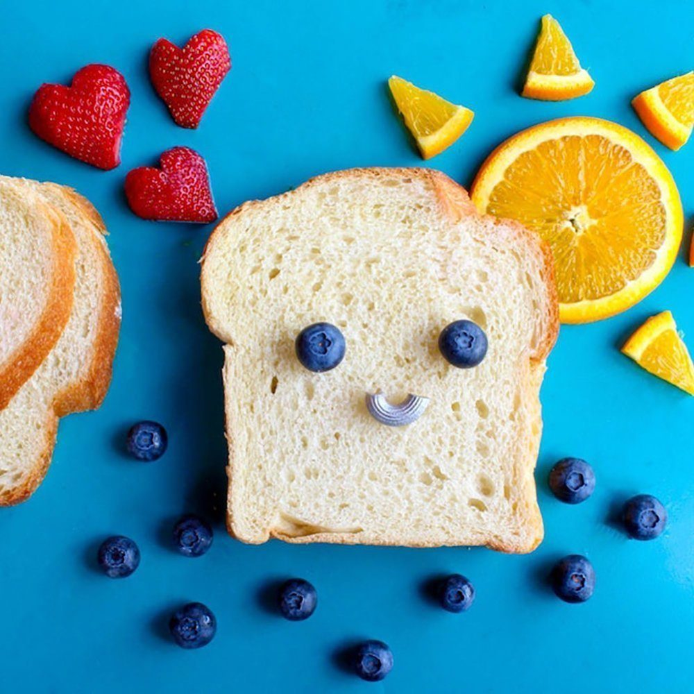 Fun photo for kids with bread dressed up to look like a smiley face using blueberries and pasta